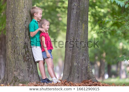 two little sister near the big tree in the forest Stock photo © Lopolo