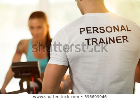 Personal trainer with young woman on cycling machine at the gym Stock photo © boggy