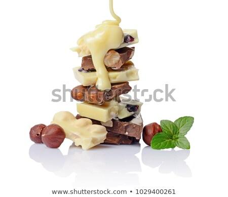 Broken milk chocolate bar with hazelnuts isolated on white. Stock photo © marylooo