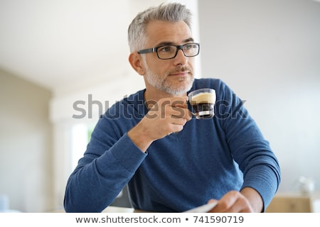 Old man drinking coffee and reading stock photo © photography33