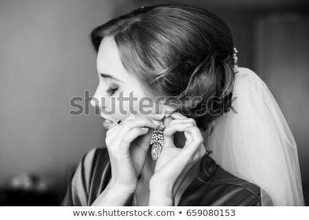 Pretty young woman putting on earrings Stock photo © dashapetrenko