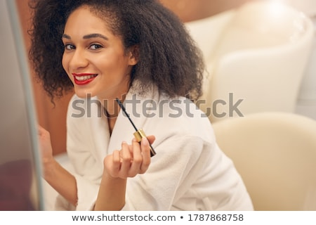 Beautiful smiling young woman in bathrobe using red lipstick  Stock photo © deandrobot