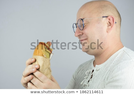 Young bearded hipster guy looking at delicious burger Stock photo © deandrobot