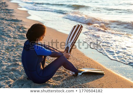 Female sitting on beach with flippers Stock photo © dash