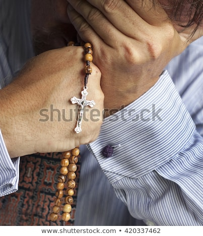 young priest holding rosary beads stock photo © gregorydean