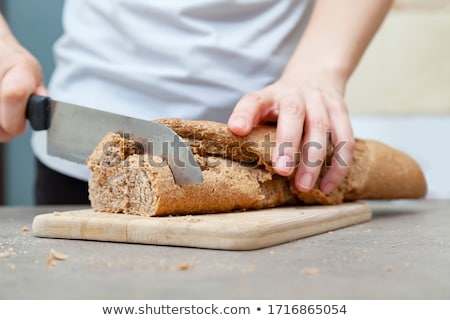 Male hands slicing fresh home-made bread on rustic table Stock photo © Yatsenko