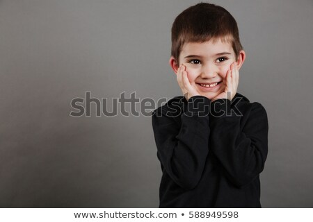 Shy happy little boy standing with hands on cheeks Stock photo © deandrobot