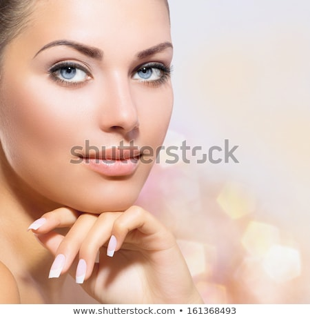 Closeup portrait of beautiful female model with blue eyes on whi Stock photo © konradbak