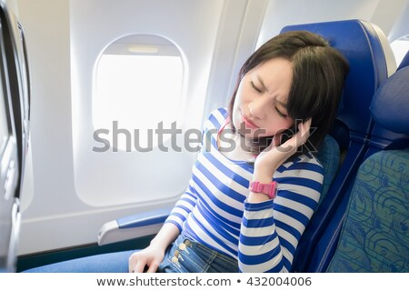 женщину сидят окна самолет чувство больным Сток-фото © NicoletaIonescu