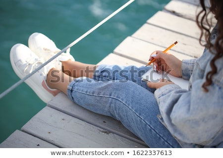 portrait of a beautiful girl sitting on the pier stock photo © tekso