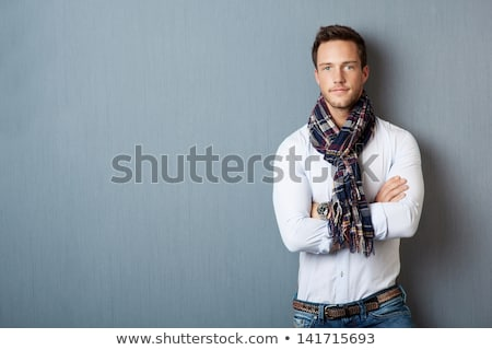 Portrait of a smart serious young man standing against white background. Emotional concept for gestu Stock photo © iordani