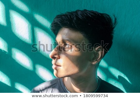man looks up with ray of light on his face Stock photo © feedough