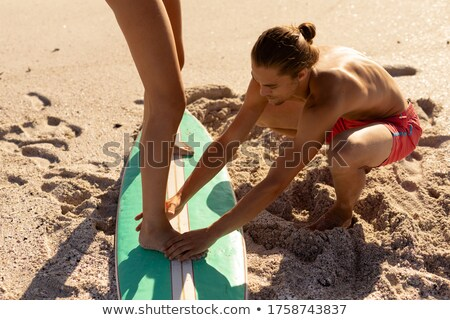 Man helping woman with surfboard Stock photo © IS2