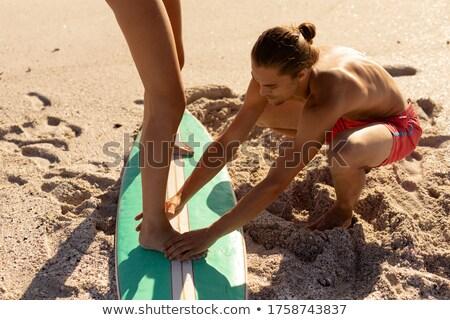 Homem ajuda mulher prancha de surfe água esportes Foto stock © IS2