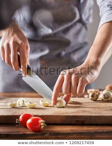 A woman in an apron slices quail eggs on a wooden board on an old wooden table. Step by Step diet sa Stock photo © artjazz