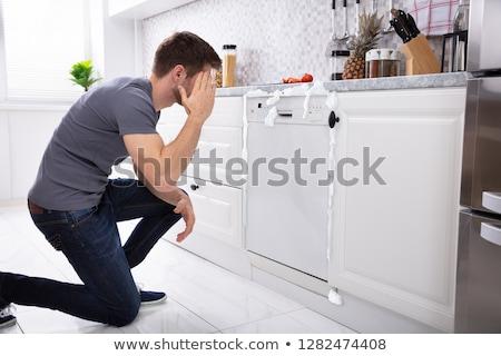 Upset Man Sitting In Front Of Damaged Dishwasher Stock photo © AndreyPopov