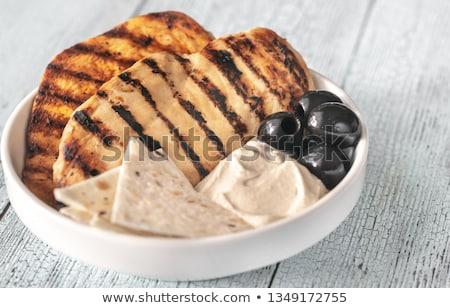 Stock photo: Grilled chicken breast with black olives and tahini sauce