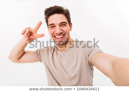 Unshaved guy in casual t-shirt smiling and gesturing hand aside  Stock photo © deandrobot
