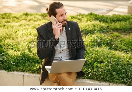 Photo closeup of caucasian business man with tied hair working o Stock photo © deandrobot