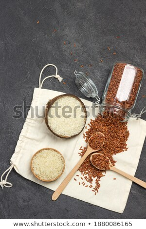 Wooden spoon and linen bag of raw organic basmati long grain and wild rice on white background. Heal Stock photo © DenisMArt