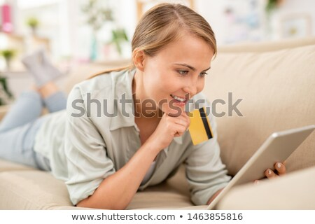 Consumer with plastic card and touchpad scrolling through online goods Stock photo © pressmaster
