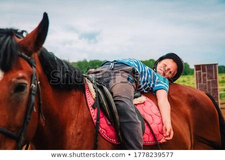 Boy horseback riding, performing exercises on horseback Stock photo © galitskaya