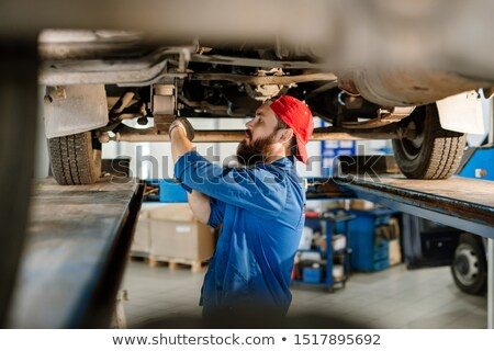Young bearded man in workwear using worktool to fix or adjust detail Stock photo © pressmaster