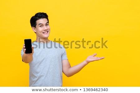 Glimlachend jonge man tonen telefoongesprek gebaar mensen Stockfoto © dolgachov
