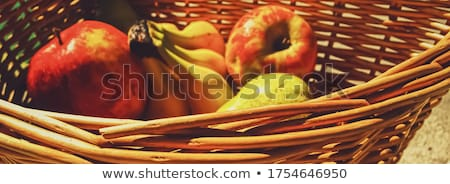 Organic apples, pears and bananas on rustic in a wicker basket Stock photo © Anneleven