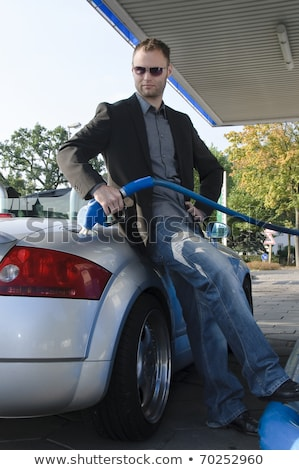 young man fueling his car at the gas station stock photo © lightpoet