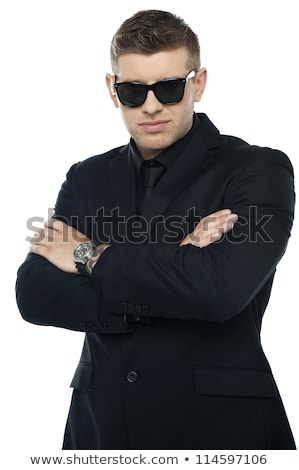 Young stylish bouncer in a black suit, arms folded stock photo © stockyimages