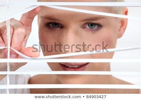 Woman peeking through some blinds Stock photo © photography33