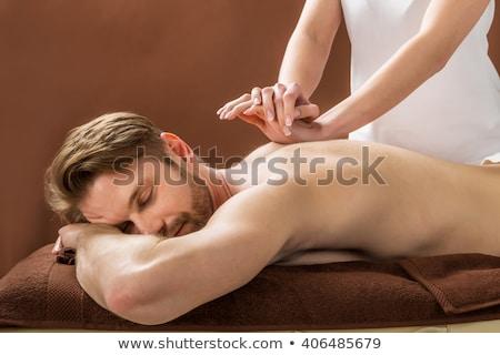 Man massaging a woman's shoulder in a room Stock photo © wavebreak_media