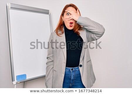 Stock photo: Happy young women peeking through a blank board