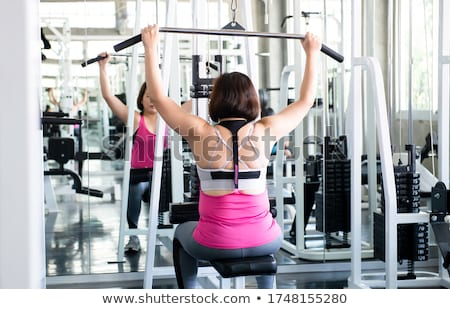lat pulldown machine woman workout at gym stock photo © lunamarina