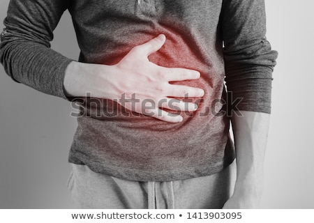 young man holding his sick stomach in pain on black background stock photo © deandrobot