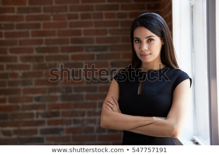 businesswoman standing with arms folded stock photo © deandrobot