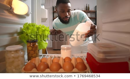 man in the kitchen with a bottle of milk Stock photo © ambro