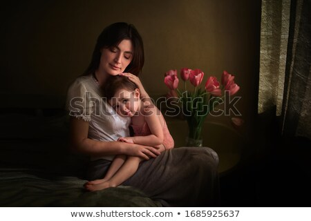 little girl together with mother sits at bed with tulips stock photo © paha_l