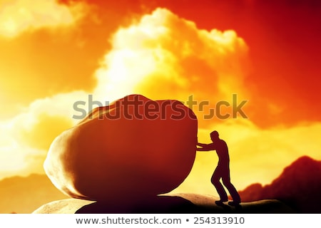 man pushing a giant heavy stone rock over the mountain stock photo © photocreo
