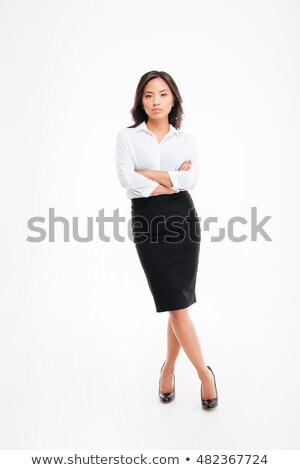 serious asian businesswoman standing with arms folded and legs crossed stock photo © deandrobot
