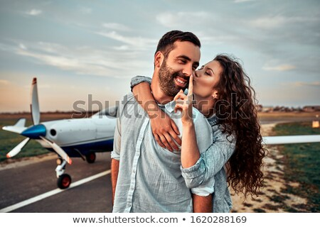Cheerful young man standing near small plane Stock photo © deandrobot
