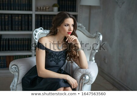 Encantador morena mujer de negocios vestido negro sesión silla Foto stock © deandrobot