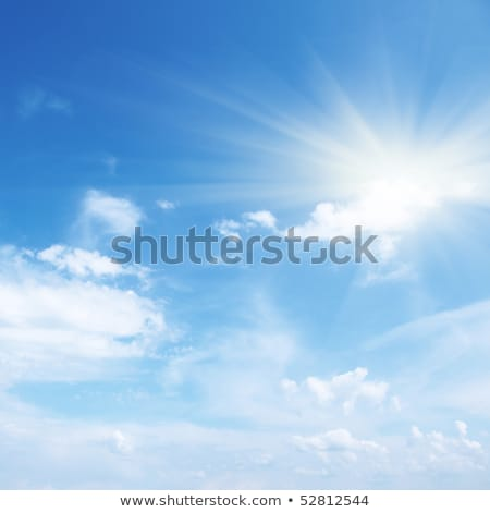 Clear blue sky with fluffy clouds and sunbeams Stock photo © TasiPas