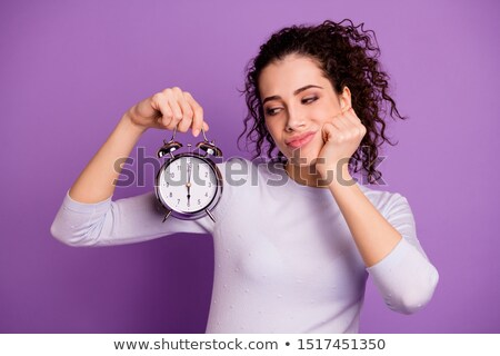 Young upset woman with curly hair holding alarm clock Stock photo © deandrobot