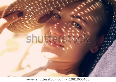 smiling young women in hats on beach Stock photo © dolgachov
