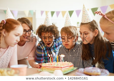 Young boy blowing out candles at party Stock photo © IS2
