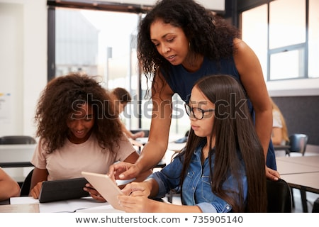 A teacher talks to a schoolboy using a computer in a high school Stock photo © monkey_business