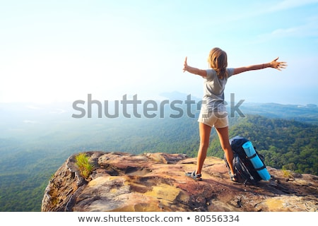 Standing young woman on the hill and looking on mountains stock photo © denbelitsky