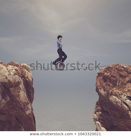 man pedaling on rope between two mountains stock photo © orla